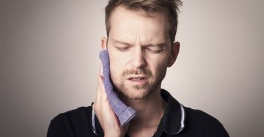 man holding a towel to his jaw