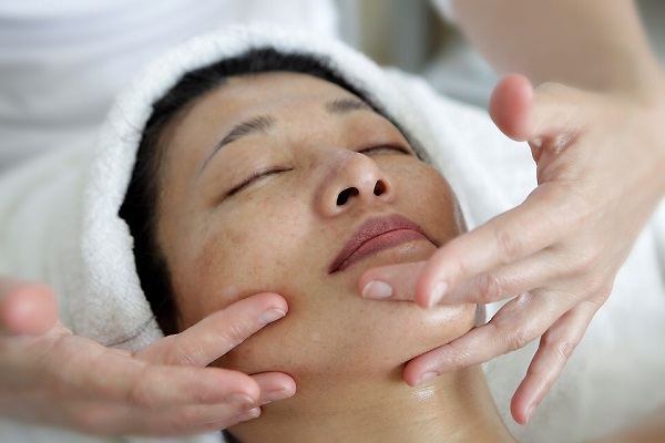 woman getting a face massage from a professional