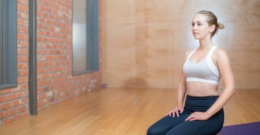 woman sitting on her knees on a yoga mat